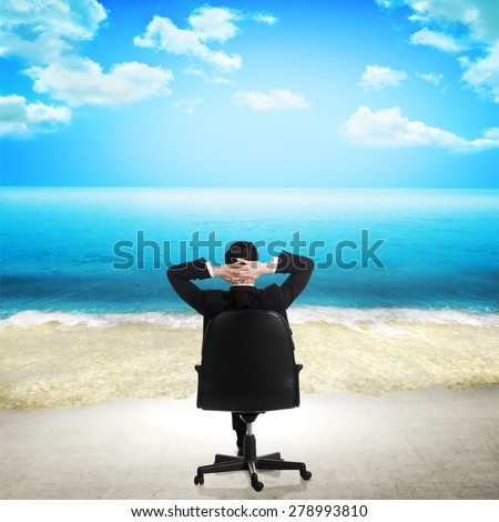Young businessman relaxing on the beach. The office floor transform into beach - stock photo