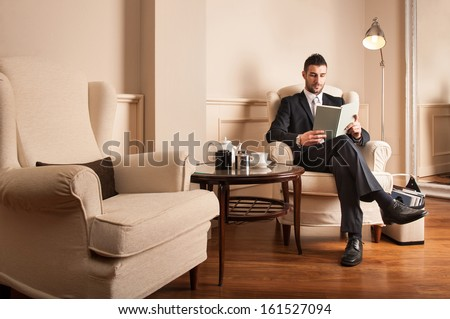 Young businessman relaxing reading a book sit on armchair.  - stock photo