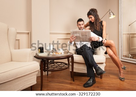 Young businessman relaxing with girlfriend while reading newspaper inside luxury hotel.