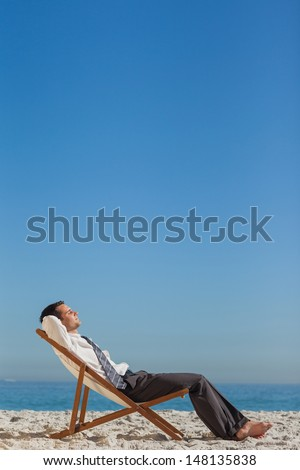 Young businessman resting on his deck chair on the beach - stock photo
