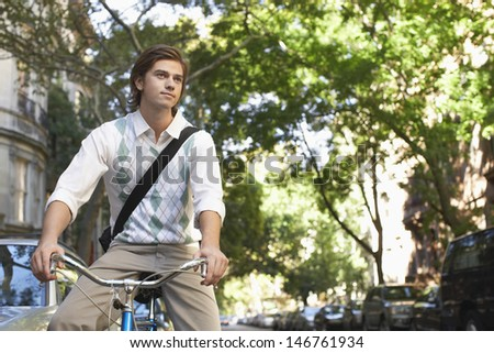 Young businessman riding bicycle on city street - stock photo