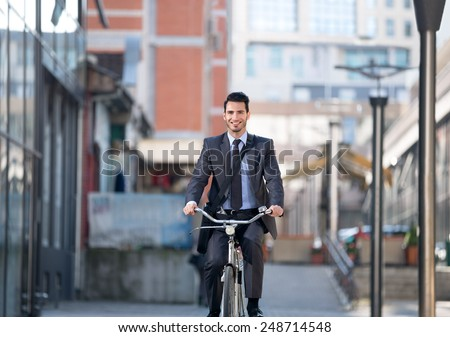 Young businessman riding bicycle on street - stock photo