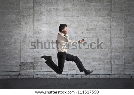 Young businessman running fast while talking on the mobile phone - stock photo
