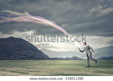 Young businessman running with book in hand