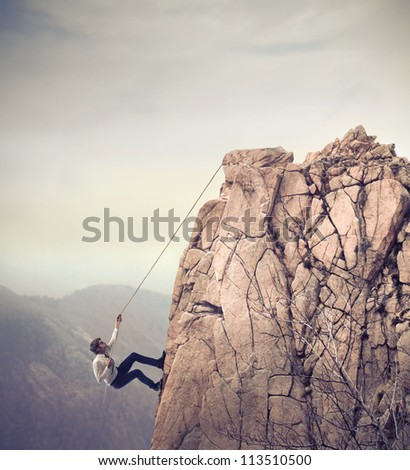 Young businessman scaling a rock - stock photo