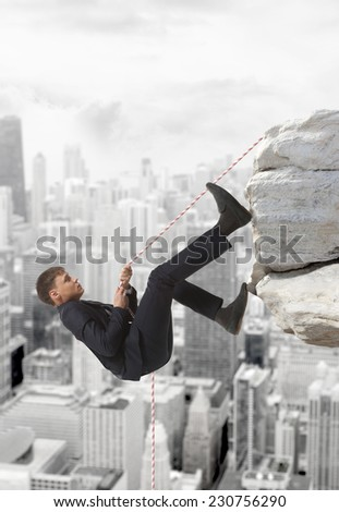 Young businessman scaling a rock   Business concept - stock photo