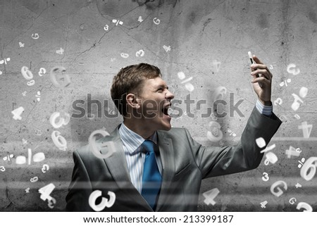 Young businessman screaming furiously in mobile phone