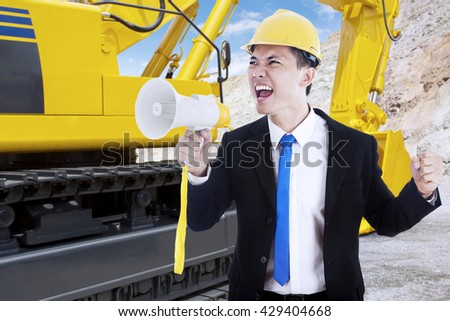 Young businessman screaming with megaphone at mining site, shot with an excavator on the background