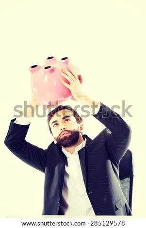 Young businessman searching money in piggybank. - stock photo