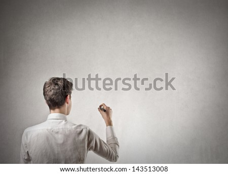 young businessman shot from behind writes - stock photo