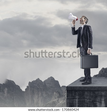 Young Businessman Shouting Through Megaphone, copy space  - stock photo
