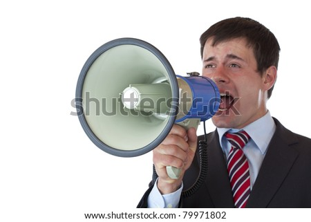 Young businessman shouts loudly into megaphone.Isolated on white background.