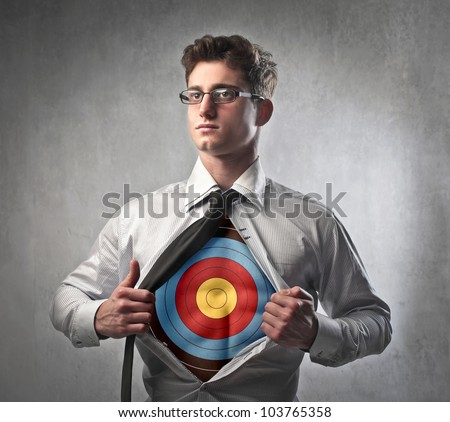 Young businessman showing a target under his shirt - stock photo