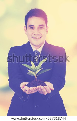 Young businessman showing an investment tree, shot with instagram filter - stock photo