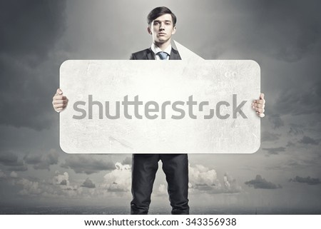 Young businessman showing blank white speech banner. Place for text - stock photo