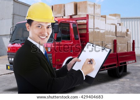 Young businessman showing clipboard while smiling at the camera with a distribution truck on the background