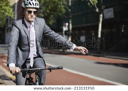 Young businessman showing hand sign while riding bicycle - stock photo