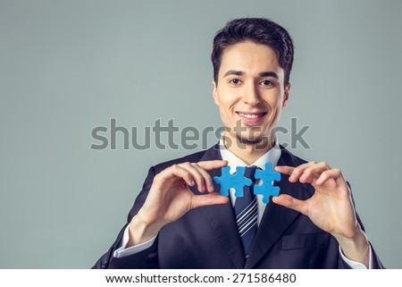 Young Businessman Showing Jigsaw Puzzle To Camera