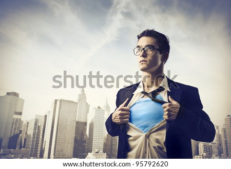Young businessman showing the superhero suit under his shirt with cityscape in the background - stock photo