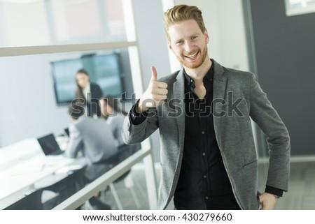 Young businessman showing thumb up - saying okay - stock photo