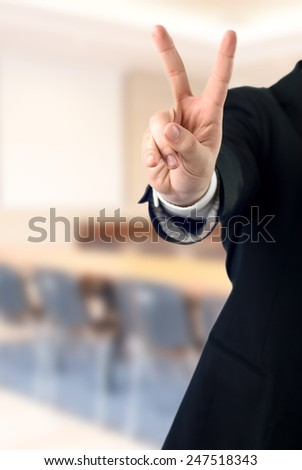 Young businessman showing victory gesture (V sign)