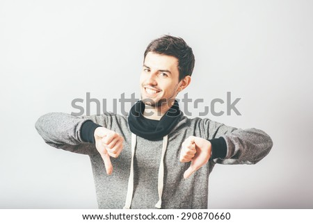 young businessman shows thumb down gesture, unhappy, sad face, studio shoot - stock photo