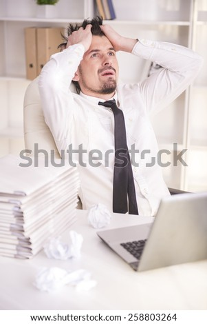 Young businessman shuts his ears with his hands while is working with laptop in his office. - stock photo