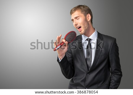 Young Businessman singing as if in microphone - stock photo