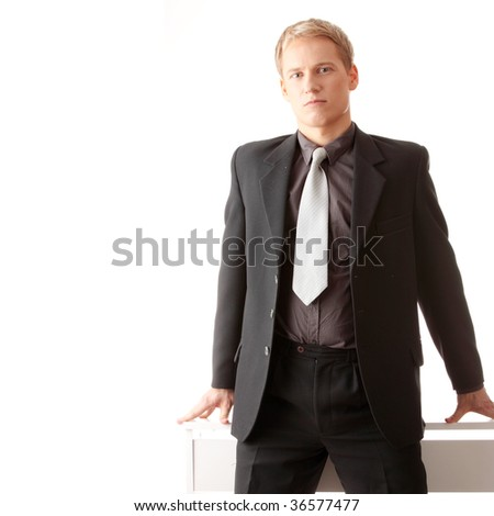 Young businessman siting on desk isolated - stock photo
