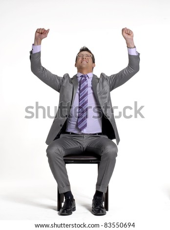 Young businessman sitting and celebrating on a chair. - stock photo