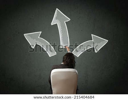 Young businessman sitting and making a decision in an office chair with different directed arrows above his head - stock photo