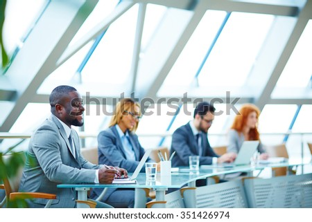 Young businessman sitting at conference on background of other employees - stock photo