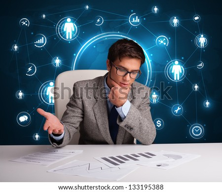 Young businessman sitting at desc with social network icons - stock photo