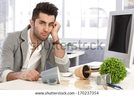 Young businessman sitting at desk desperate after burst of anger. - stock photo
