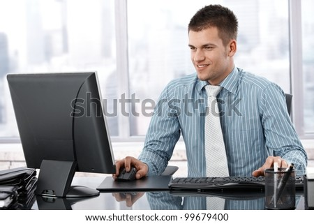 Young businessman sitting at desk in modern office, working on computer, smiling. - stock photo