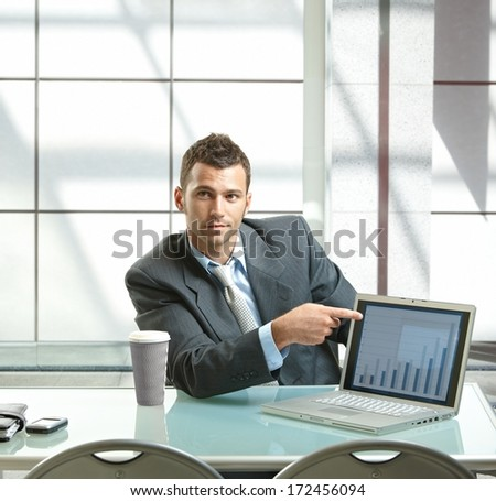 Young businessman sitting at desk presenting business diagram to others on laptop computer. - stock photo