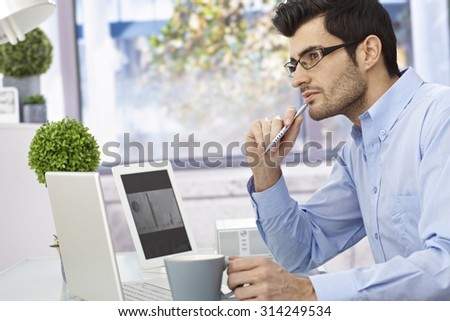 Young businessman sitting at desk, thinking, using laptop computer and tablet. - stock photo