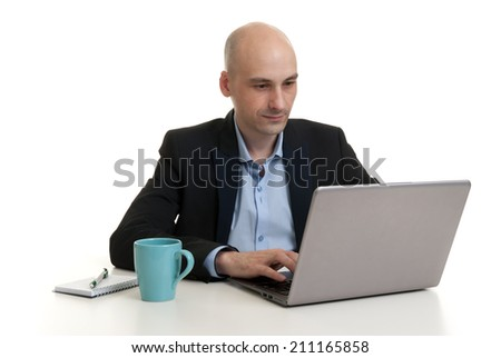 Young businessman sitting at desk, working on laptop computer - isolated - stock photo
