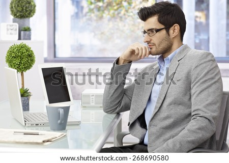 Young businessman sitting at desk, working with laptop computer, looking at screen. - stock photo