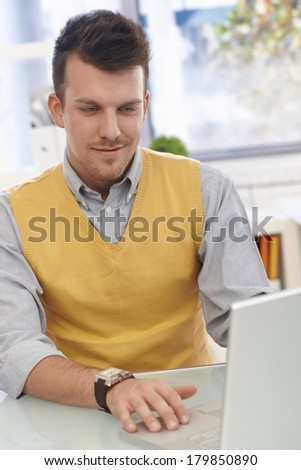 Young businessman sitting at desk working with laptop computer, smiling. - stock photo