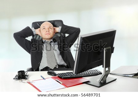 Young businessman sitting at his desk in the office.