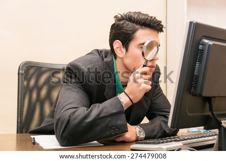 Young businessman sitting at his desk searching through magnifying glass in front of  computer - stock photo
