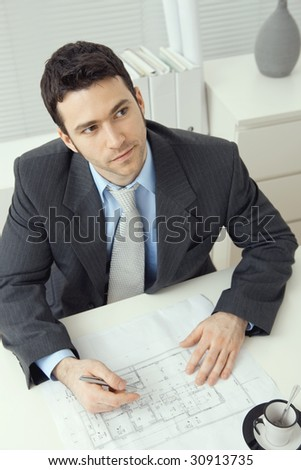 Young businessman, sitting at office desk, planning office layout. Overhead shot.