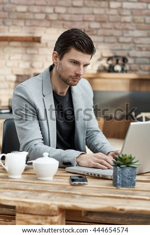 Young businessman sitting at table, working with laptop. - stock photo