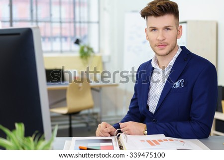 young businessman sitting at the desk in a modern office