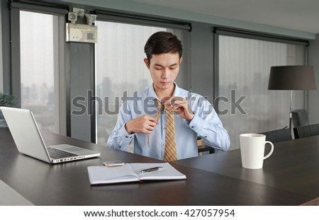 Young businessman sitting at the table and wearing necktie