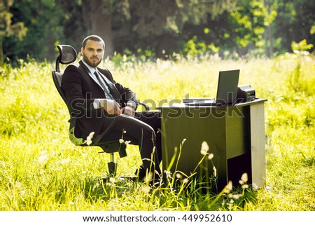 Young businessman sitting at the table in the park. Beautiful background.