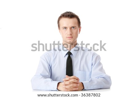 Young businessman sitting behind the desk isolated