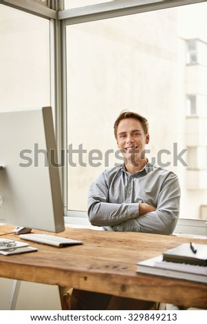Young businessman sitting confidently with his arms folded behind his desk in a bright office