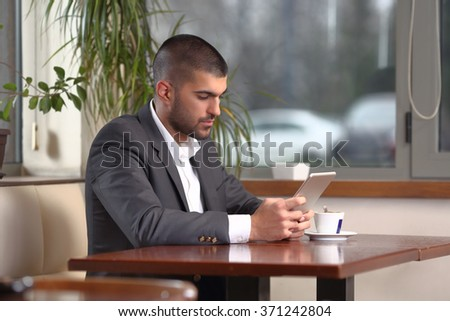Young businessman sitting in a caffe using digital tablet